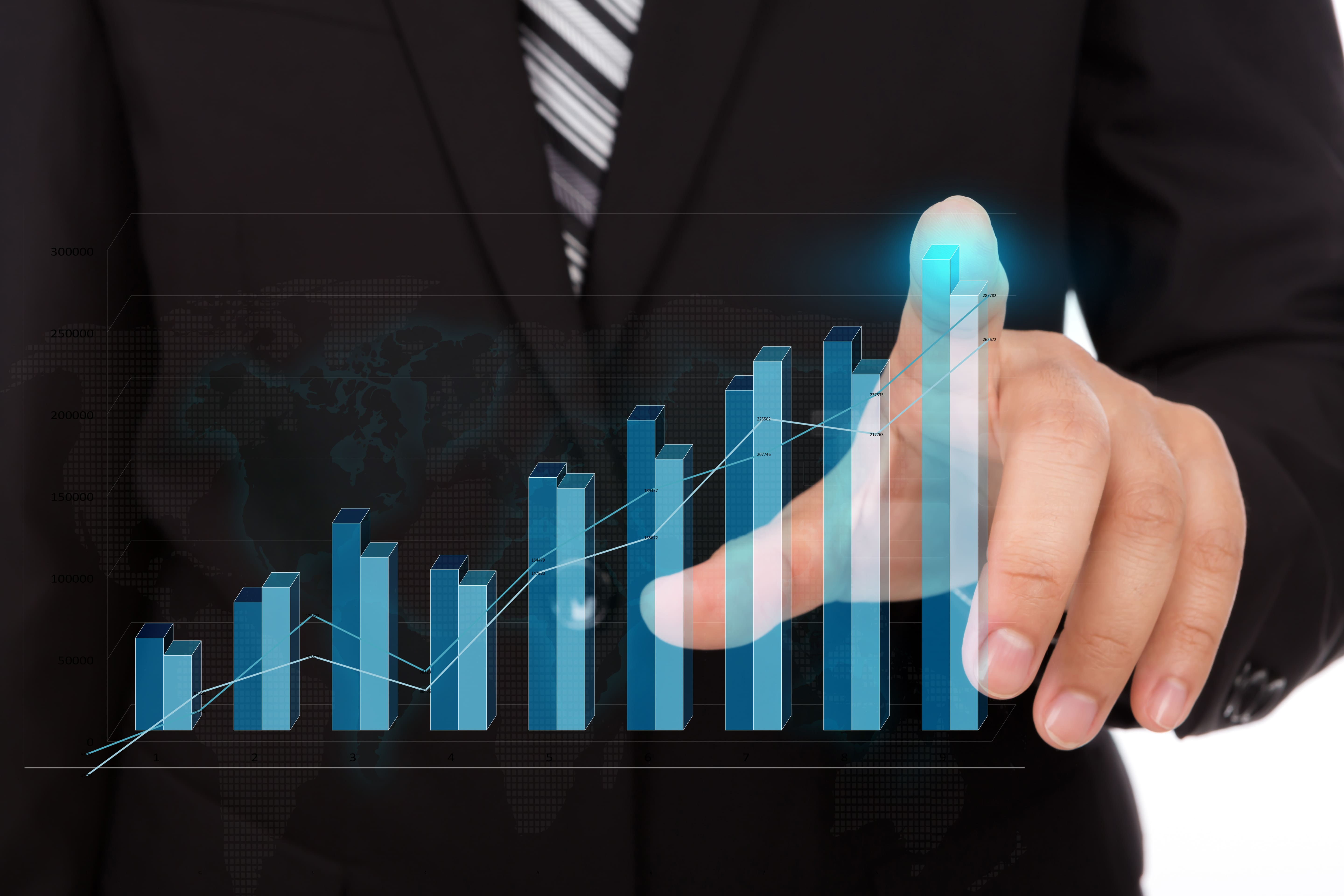 businessman touching the tip of a bar chart 1
